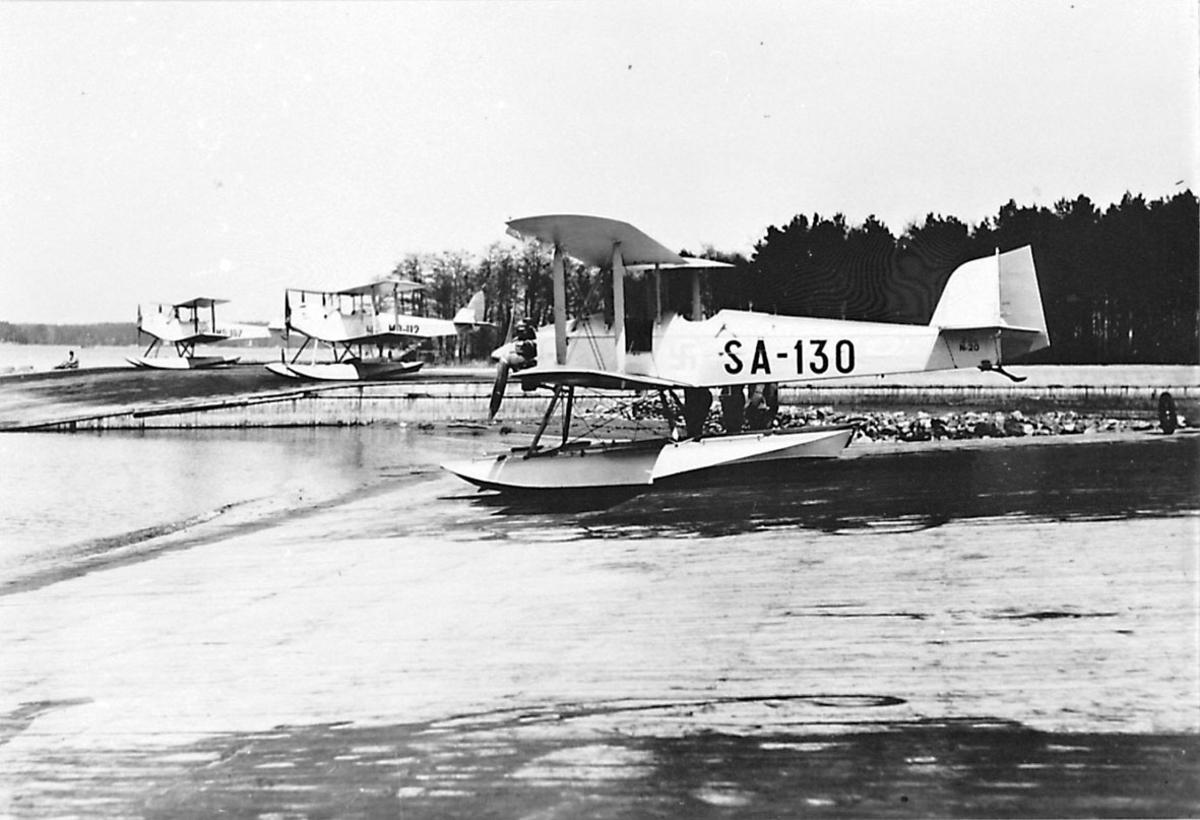Fly, propellfly, dobbeldekker, Sääski SA-130, foran. Sjøflyhavn med flere 3 sjøfly som står på land.