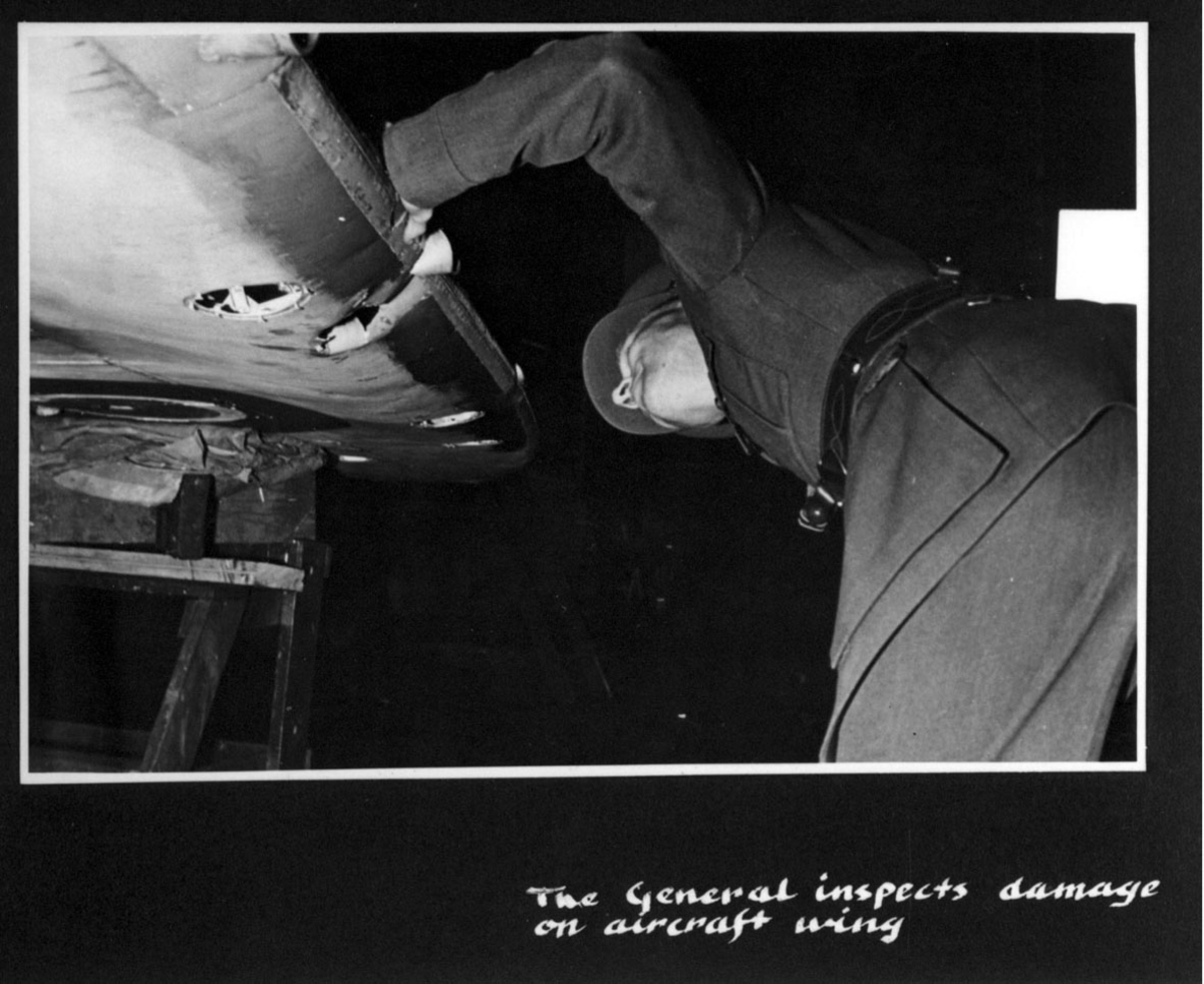 Person i militæruniform, studerer skadet vinge på et fly. (Ant. General W. Hansteen).