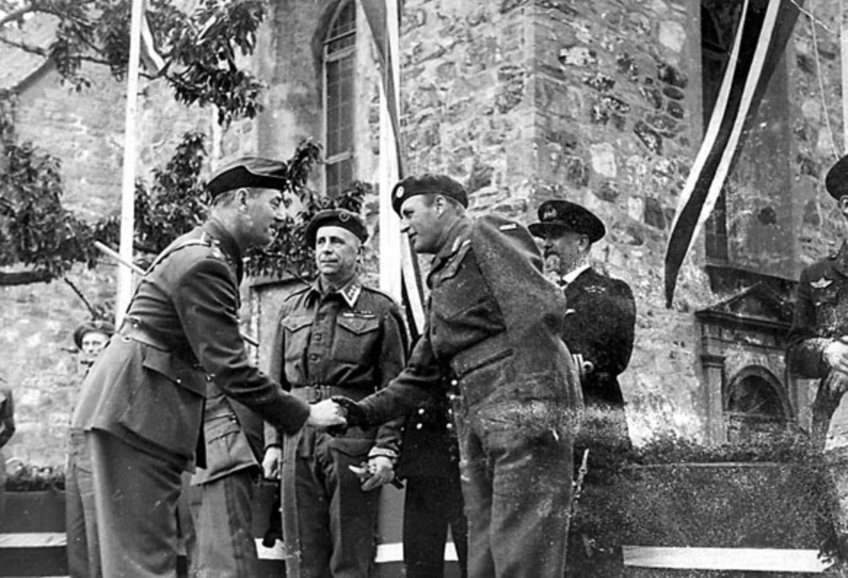 Portrett, 6 personer, militære, i militæruniform foran større murbygning (Nidarosdomen?). Kronprins Olav hilser på øverstkommanderende for de allierte styrker i Trondheim.