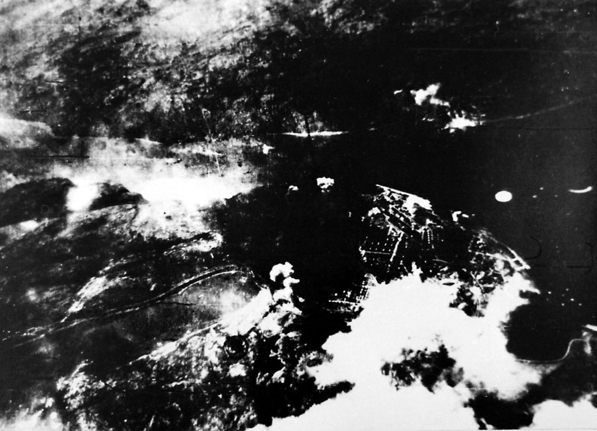Luftfoto. Tettsted under med røyk fra bygninger i brann, etter bombing av området.