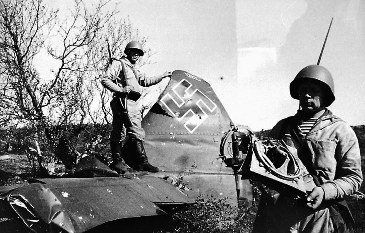Portrett. 2 soldater i militæruniform. Begge med gevær på ryggen. Står ved et ødelagt fly, Ju 88 A-5 (W.Nr.2341, 4D+AC?). Hakekors påmalt halepartiet.