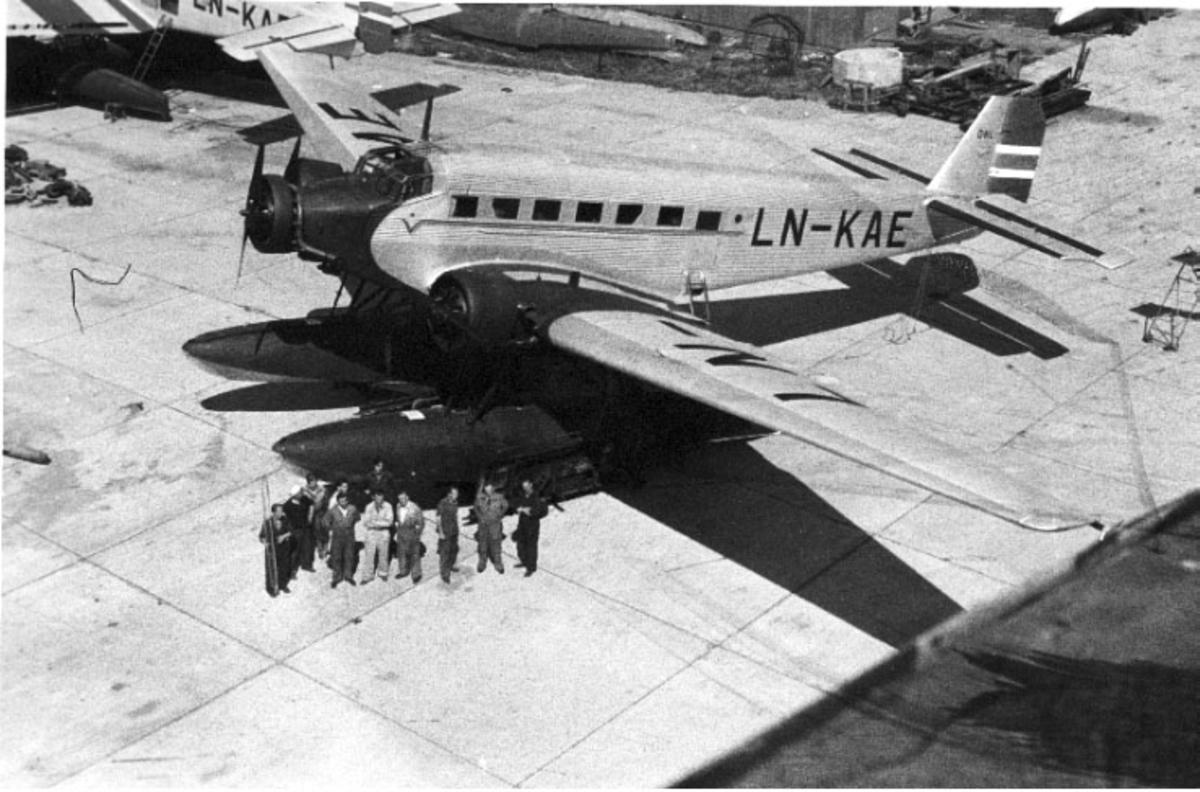 """1 fly på bakken, Junkers JU 52 3mg3e, LN-KAE """"PÅL"""", sett ovenfra. Flere personer står oppstilt ved den ene flotttøren. Litt av annet fly bak."""