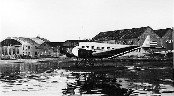 1 fly, Junkers Ju 52 3mg3e, LN-KAI, i sakte fart på havoverflate, sett fra siden, nær land. Flere bygninger bak.