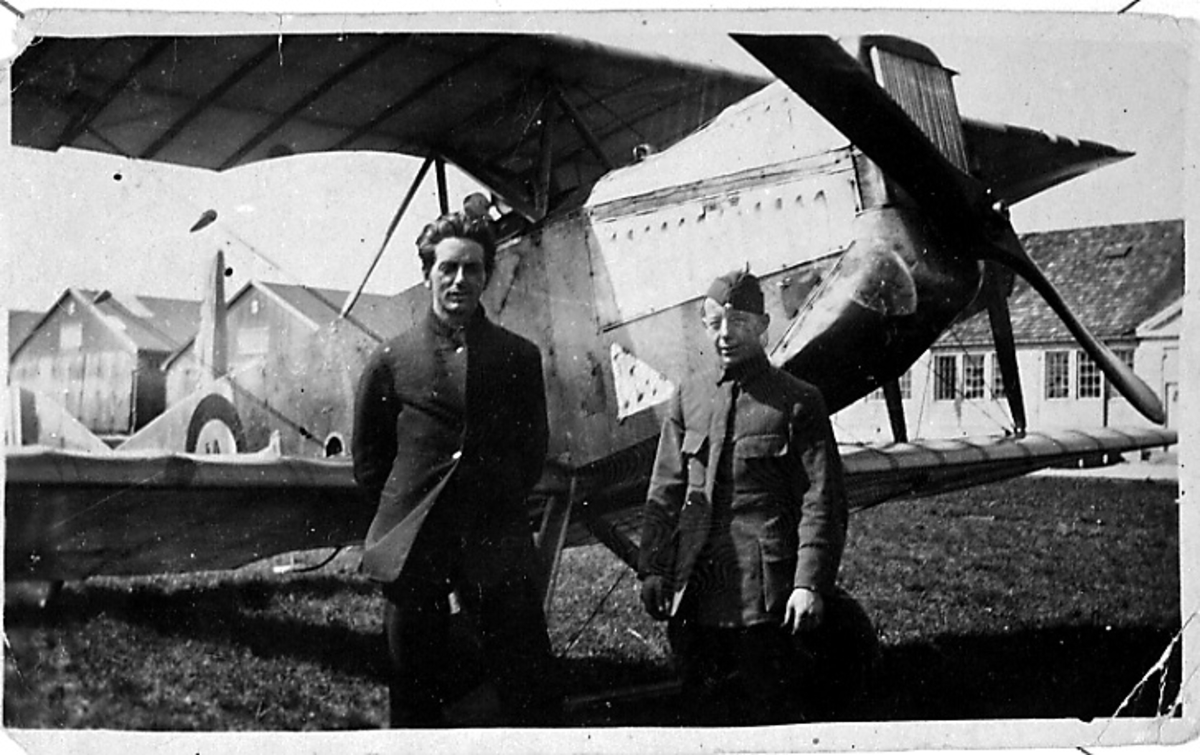 1 fly på bakken, Kaie nr. 41, skrått forfra, to personer, militære, i militæruniform, står foran. Bygninger bak.