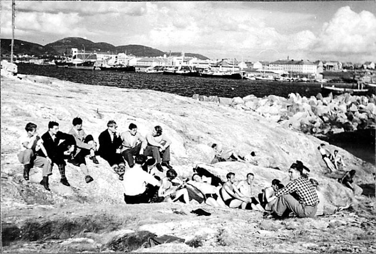 Portrett, flere personer sitter på et berg i forgrunnen. Havneområde bak med flere fartøy ved kai. Lit av molo sees.