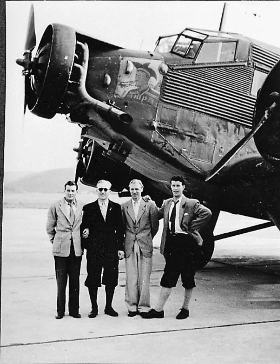 """Portrett, 4 personer stå foran et fly, Junkers """"Jåmpa""""? (bilde av same på nesepartiet)"""