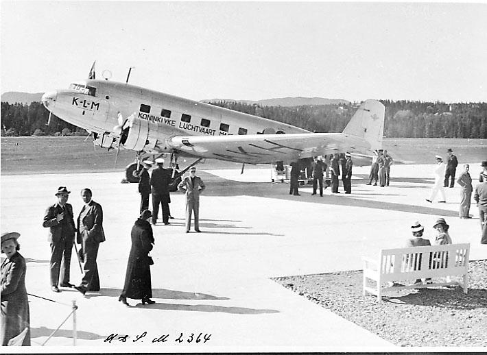 """Lufthavn, 1 fly på bakken, DC-2 PH-AKH """"HAAN"""" fra KLM. Skrått fra siden. Flere personer ved flyet."""