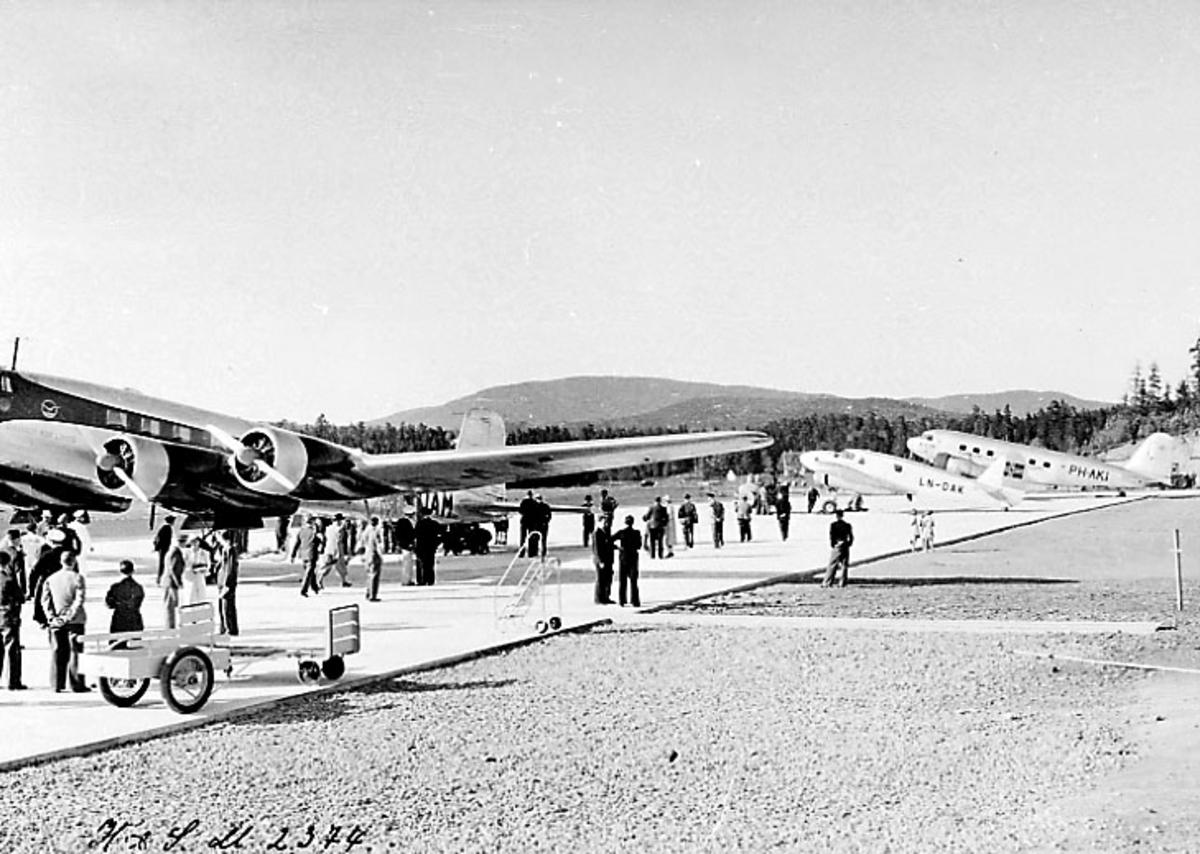 """Lufthavn, 3 fly på bakken, flyet foran, Focke-Wulf Fw200 Condor OY-DAM """"Dania"""" fra DAL (DDL). Flyene bak har reg.nr LN-DAK og PH-AKI. Mange personer ved flyene."""