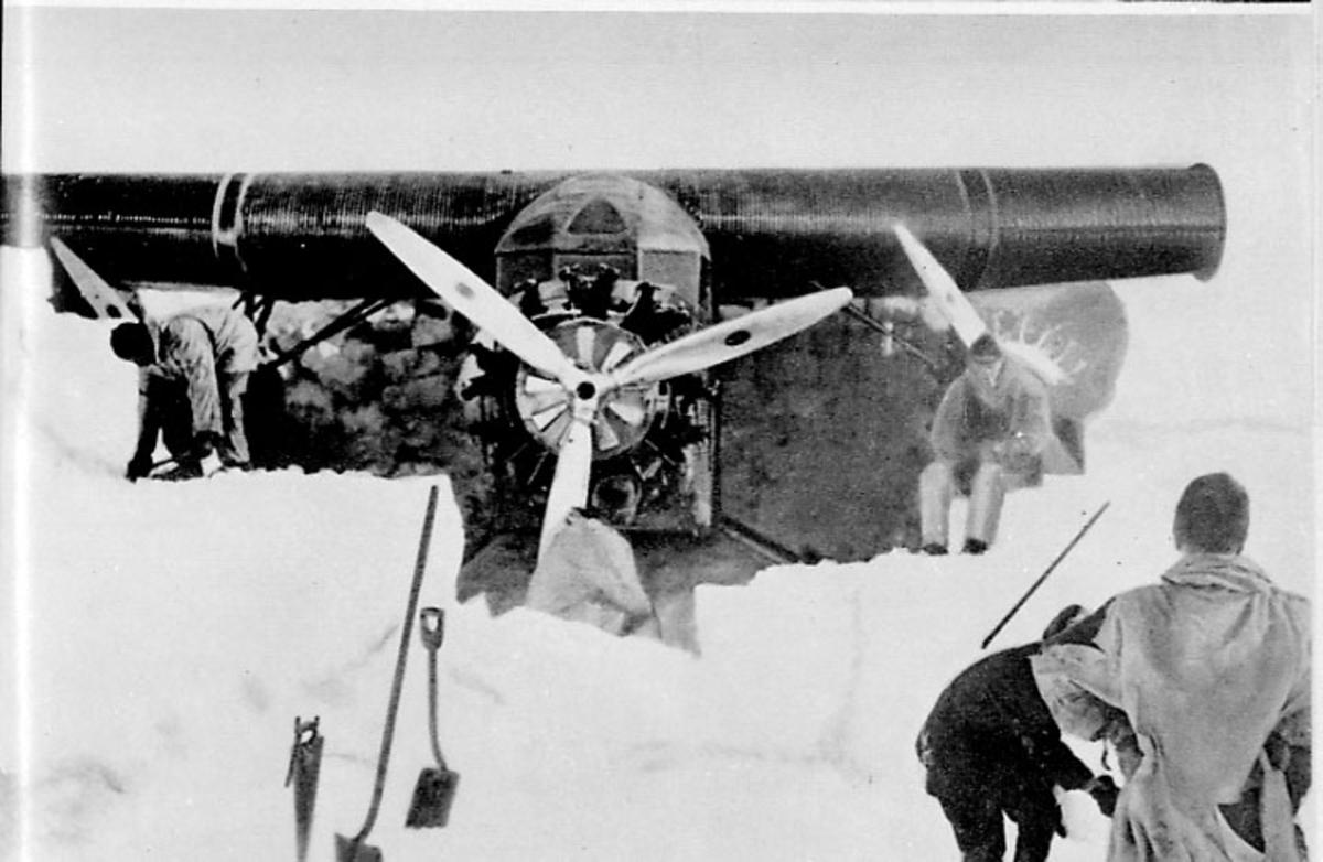 1 fly delvis inneforsset i isen. Noen personer ved flyet.