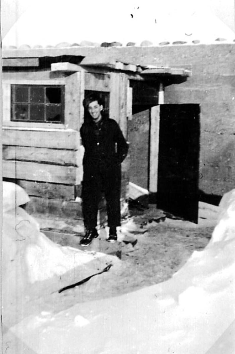 Portrett av 1 person, oppstilt foran ei mindre bygning. Tatt utendørs. Snø på bakken.