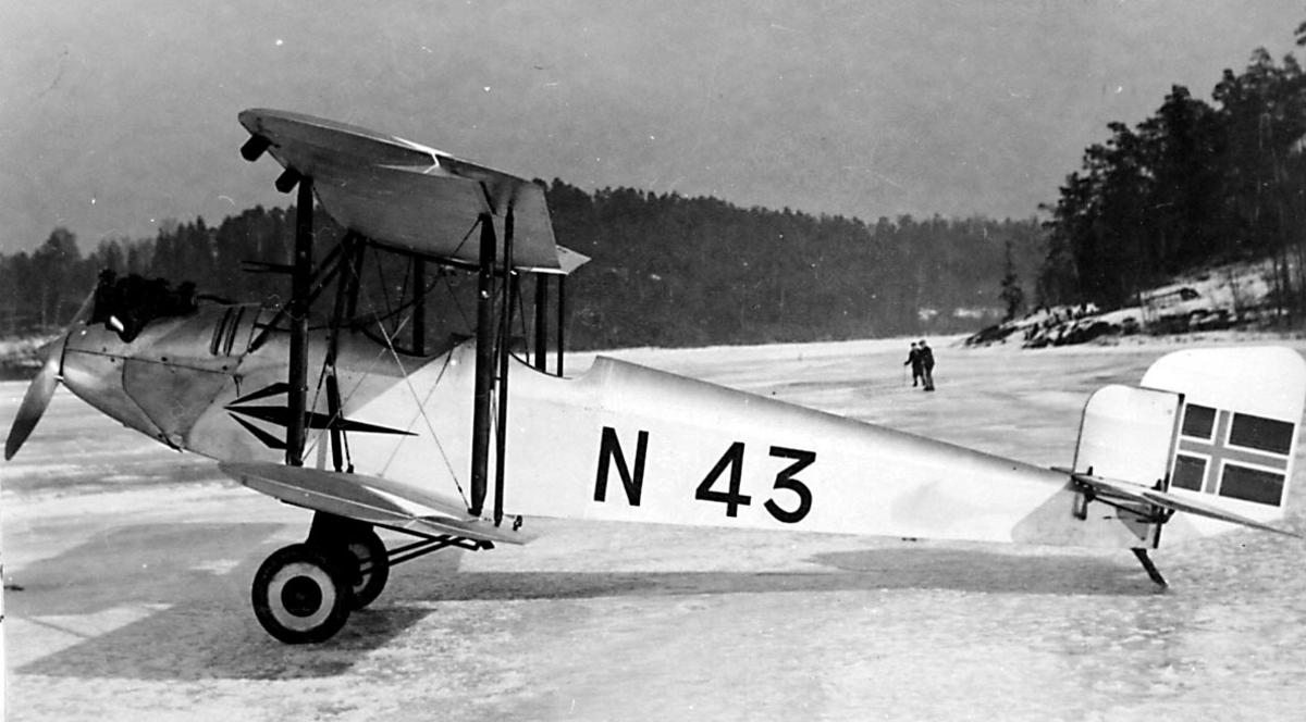 1 fly på bakken, islagt vann, Simmons Spartan I, N.43 LN-ABG fra Viggo Widerøe, Oslo. 2 personer i bakgrunnen.
