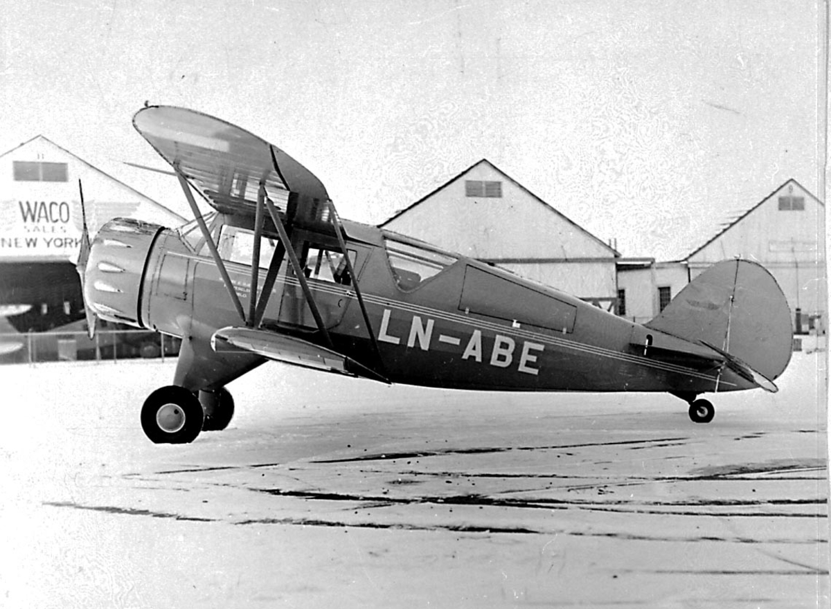 1 fly på bakken foran flere hangarbygninger, Waco UTC, LN-ABE fra Widerøe & Bjørneby.