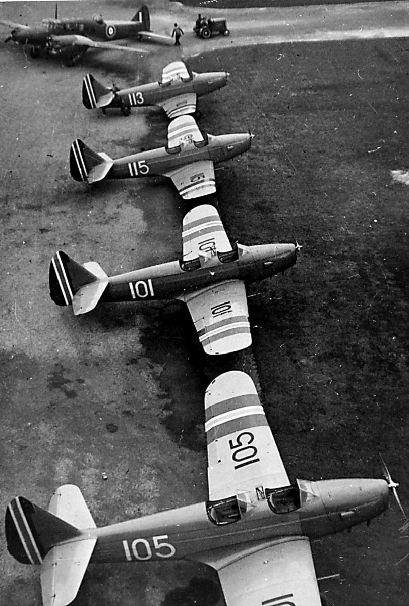 Lufthavn. 4 fly på rekke Fairchild M-62A, 105, 101, 115, 113 fra Hærens Flyvåpen i Toronto. 1 annet fly i bakgrunnen + 1 traktor.