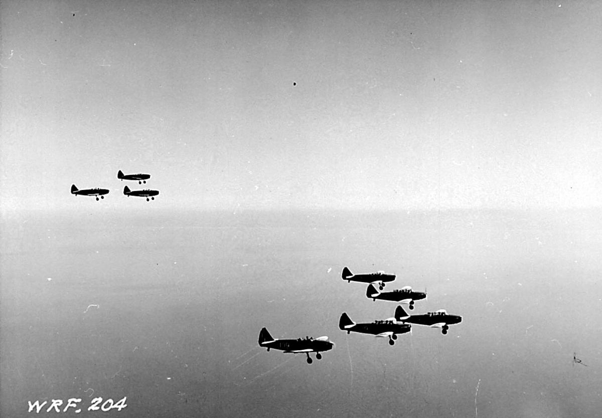 Luftfoto. 8 fly i formasjon Fairchild M-62A, fra Hærens Flyvåpen i Toronto.