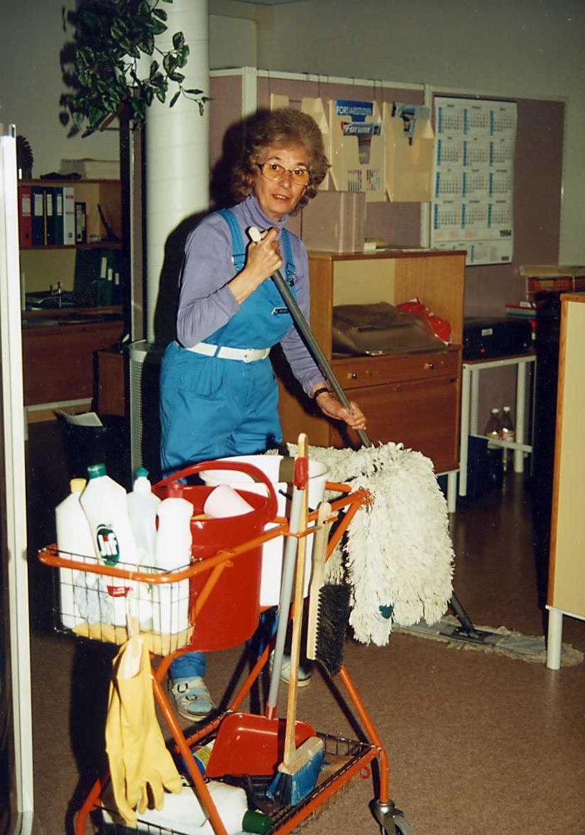 Portrett. En renholdsbetjent med utstyr vasker gulv på et kontor.