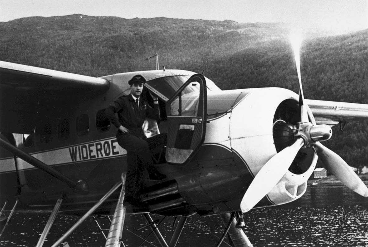 1 fly på bakken, DH Otter fra Widerøe. 1 person, mann i flygeruniform ved flyet.(T.Romsloe)