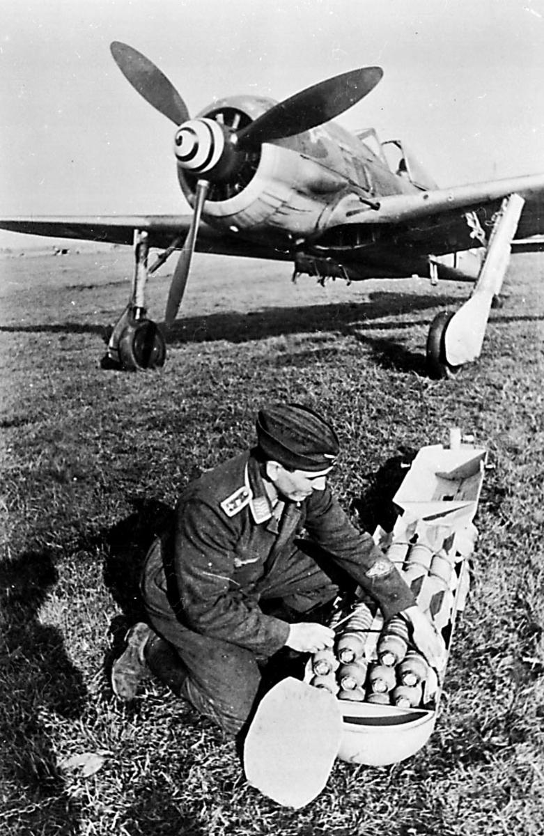 Portrett, 1 person, militært personell, fra Luftwaffe, sitter ved siden av flere bomber, foran 1 fly, Ju87 Stuka.