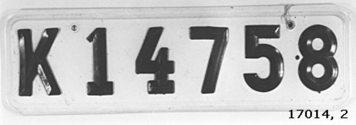"""Skylt av plast, vit botten, svarta bokstäver och siffror fastnitade """" K 14758 """"."""