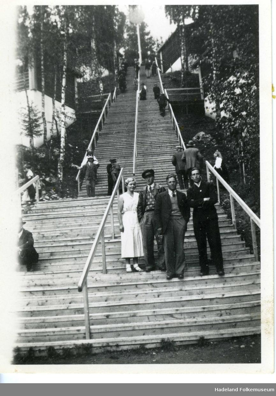 Tre menn og en kvinne ved foten av en lang trapp.