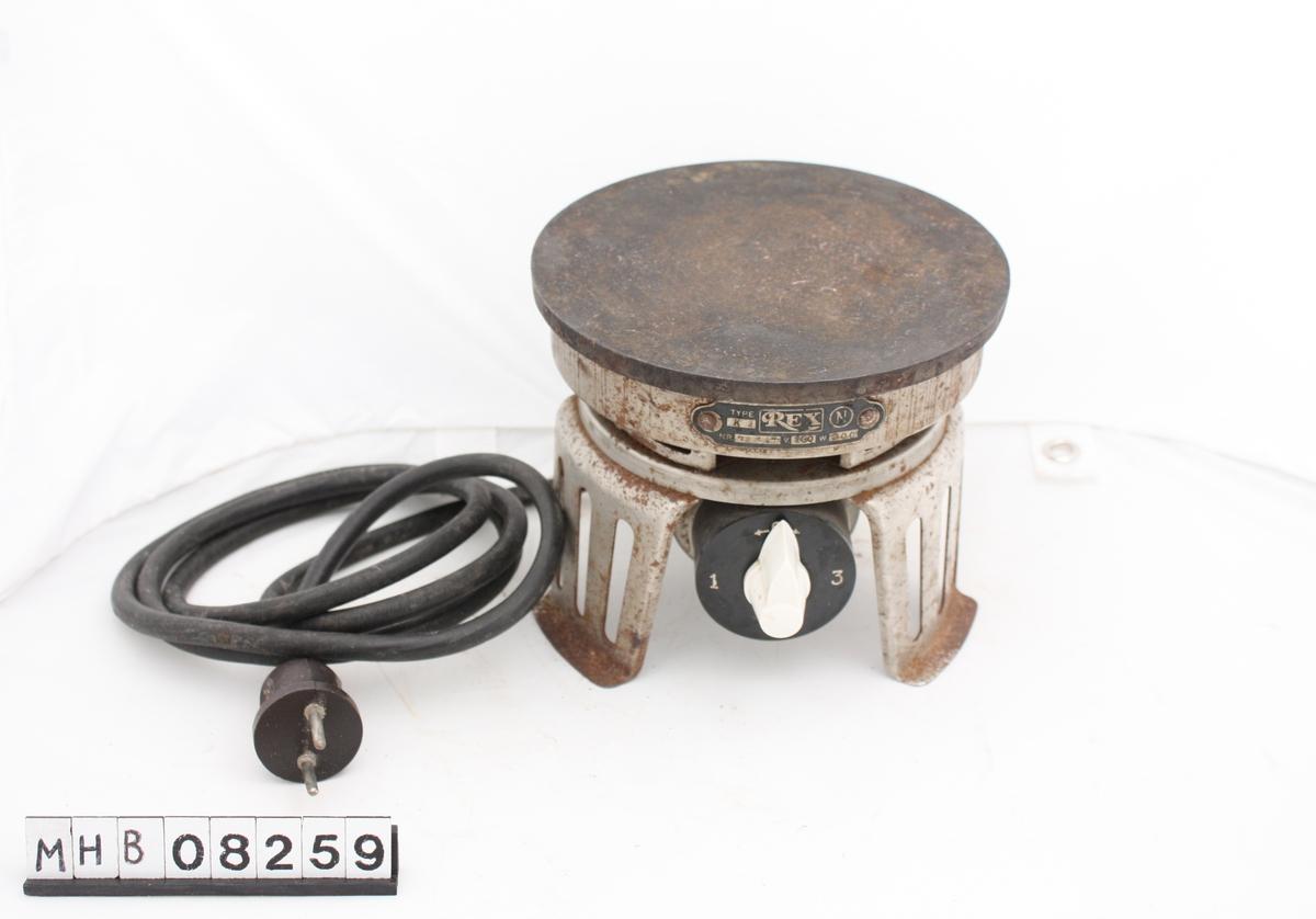 Elektrsik plate med ledning. Understell av blek   Merke: REX. 230 (?) V, 300 (?) W.