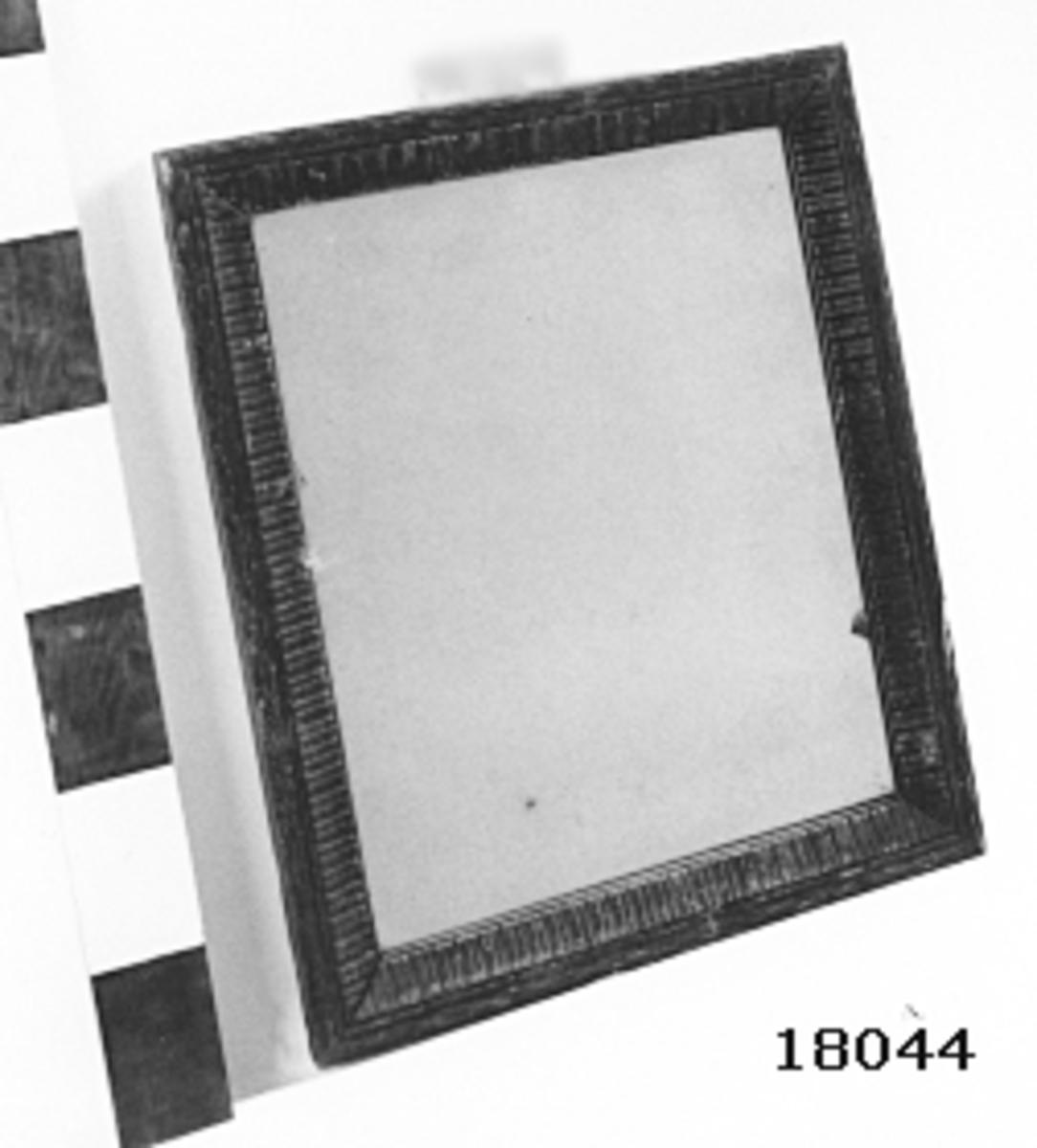 """Rektangulär spegel med profilerad träram, ornerad, B = 50 mm. Baksida försedd med brädor, öglor för upphängning till skott. Öglorna har sekundär placering. Märkt: Inbränd kronostämpel, skrivet med blyerts """" Skirner """""""