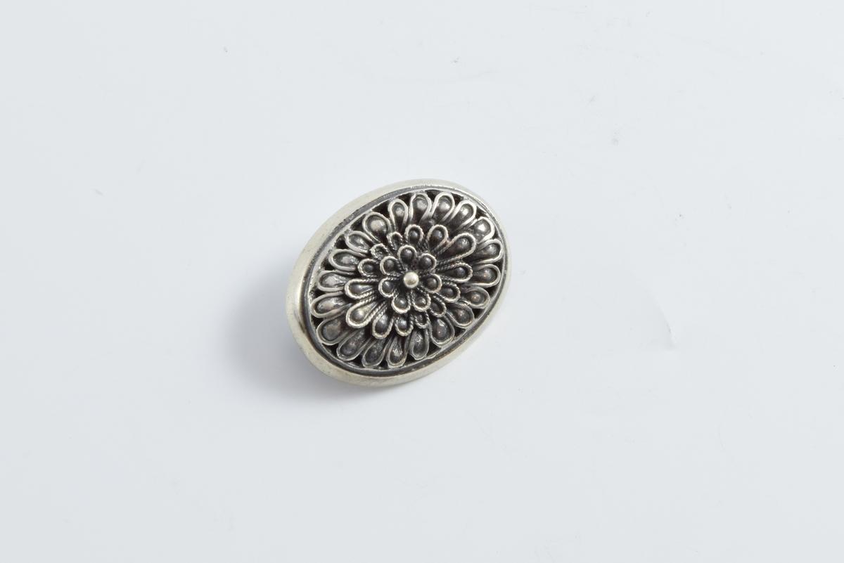 Oval nål med rosett på forsiden og nålefeste på baksiden