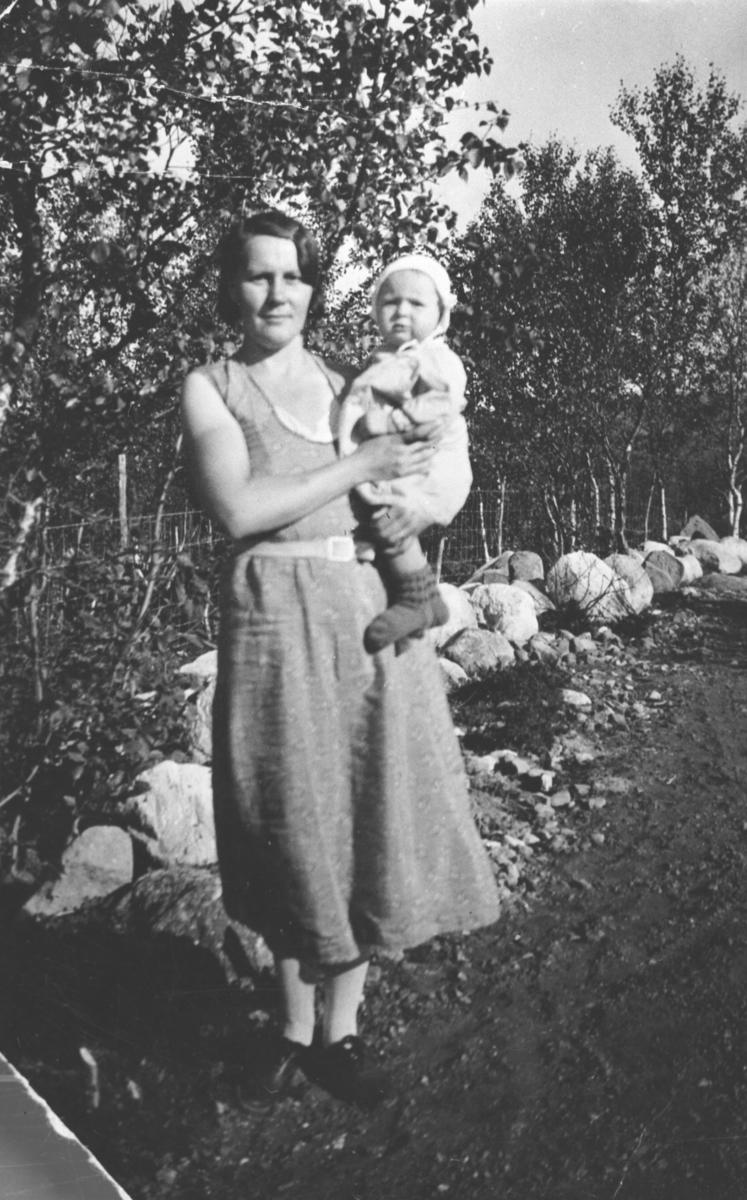 Kaija Johnsen står i grusveikanten foran bjørketrær med et spedbarn, datteren Anny Johnsen, i fanget. Dagen er solig og det er sommer. Kaija er kledd i kortermet sommerkjole.