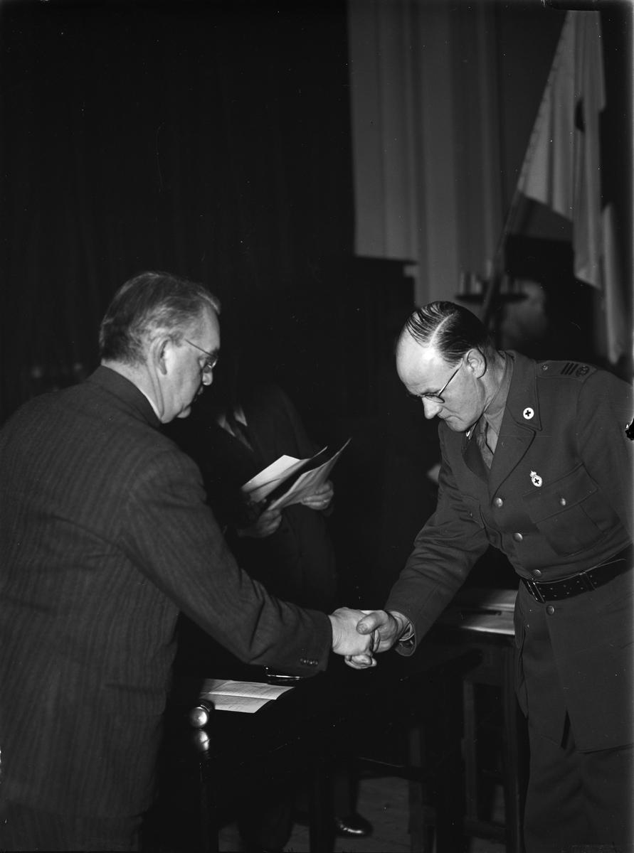 Landshövding Hilding Kjellman skakar hand med uniformsklädd man med märken från Röda Korset, Uppsala i februari 1944