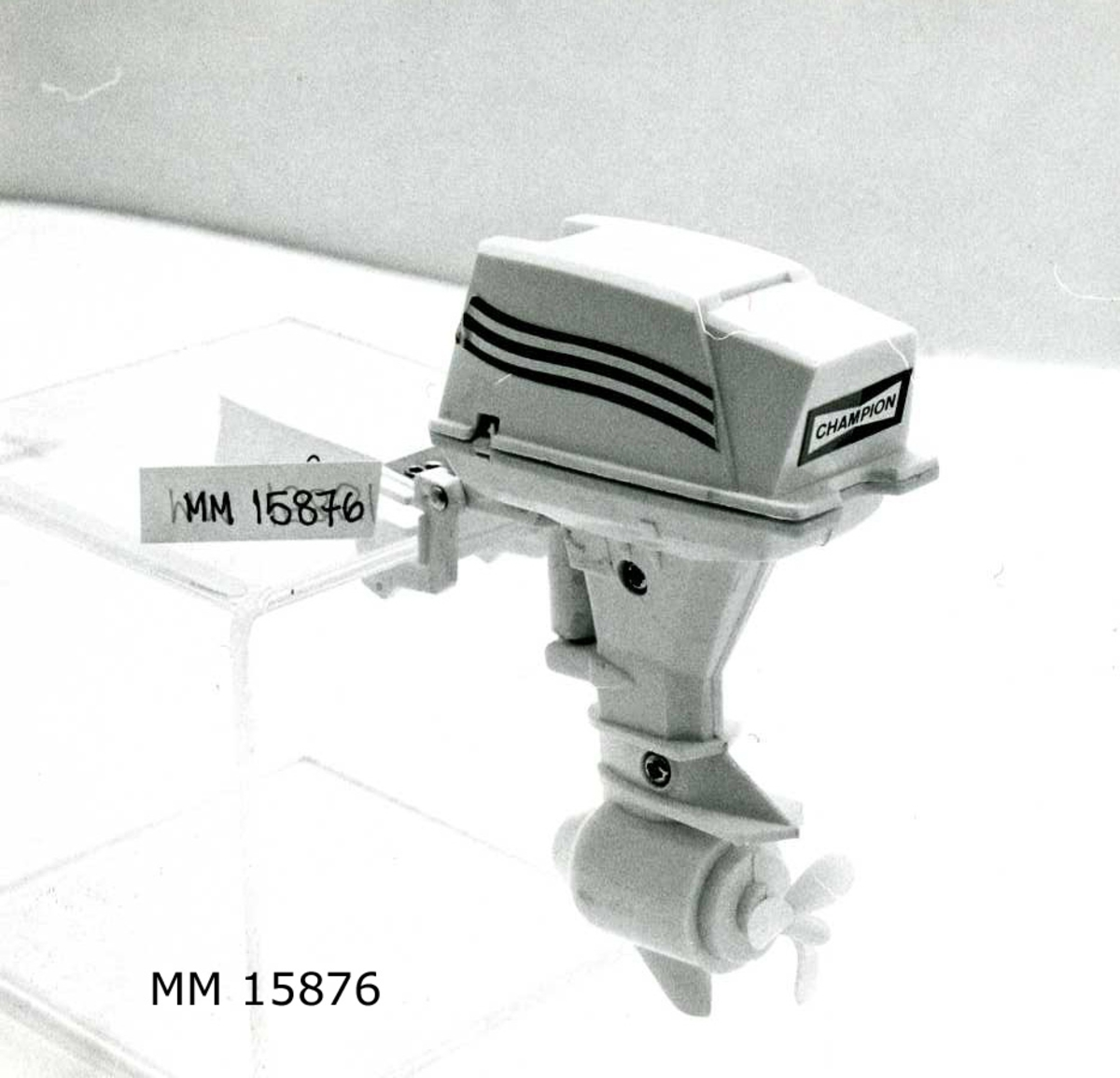 """Modell av utombordsmotor i vit plast. På motorn övre del röd-vita fartlinjer på två sidor, samt en skylt med texten """"Champion"""". Motorns övre del som är löstagbar utgör batterifästet för 3 st stavbatterier. Själva el-motorn sitter inkapslad vid propellern. Motorns fästanordning som består av en u-formad plastbit med skruv kan föras upp och ner samt i sidled."""