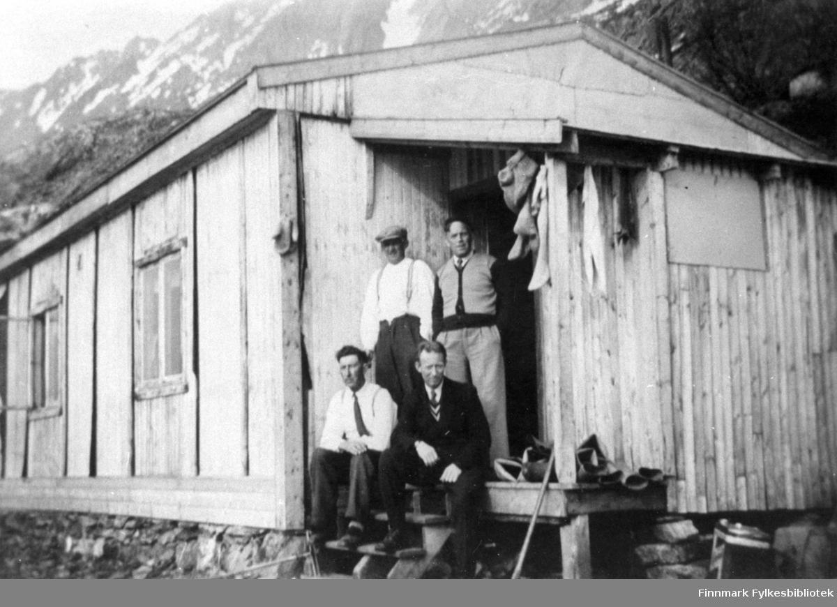 Portrettfotografi av en gruppe på trappa til en brakke. Sittende fra venstre: Odin Emaus og Agnar Iversen. Stående fra venstre: Håkon Rapp og Håkon Iversen.