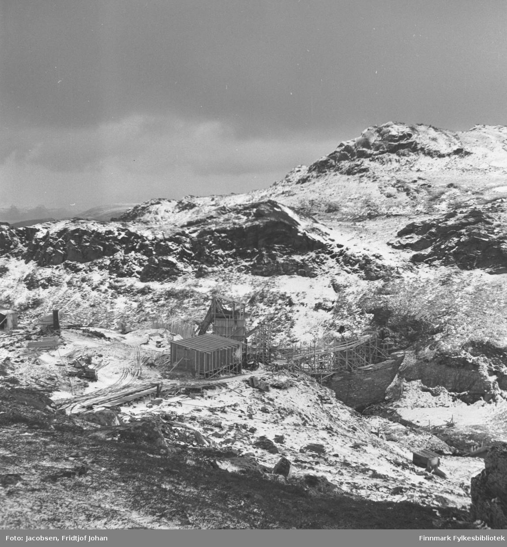 Glimmevannsdemningen ovenfor Hammerfest under bygging/reperasjon. En brakke er satt opp ved siden av demningen, muligens en arbeidsbrakke. Terrenget er kupert og har fått et tynt snølag.