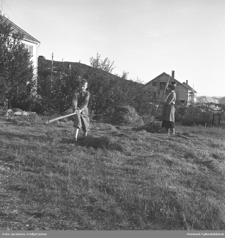 Aase Jacobsen og sønnen Arne steller i hagen på eiendommen til Arne Nakken, far til Aase. Begge to har river i hendene og raker gress. Arne har en ganske lys bukse og jakke på seg. Aase har et mørkt skjørt og lys kåpe. Flere løvtrær står øverst i hagen og en del av Nakkens hus ses til venstre på bildet. En bygning kan skimtes gjennom trærne og flere hus står lengre bort på området .