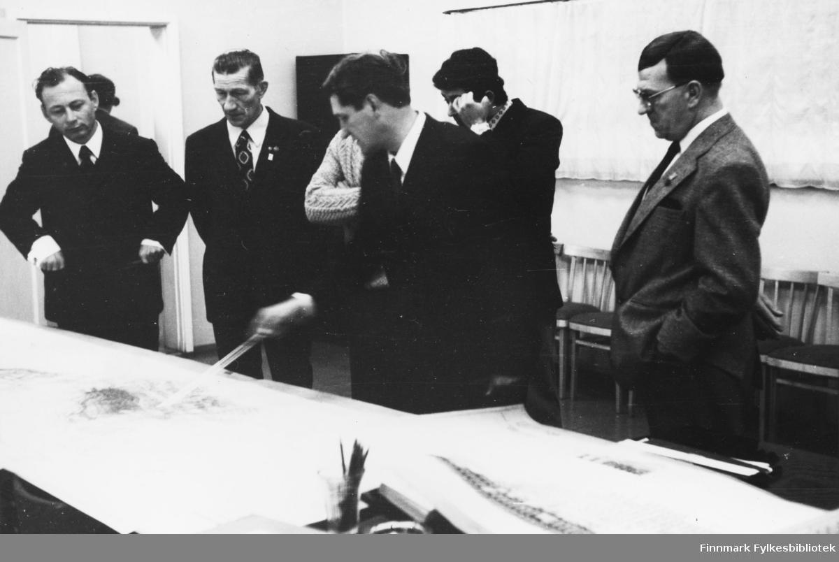 Bilde fra en gruve/fagforeningsutveksling i Nikel, Russland på 1970-tallet. Fra venstre står: en ukjent russer, Gunnar bakkeslett, Martin Seljemo (delvis skjult), ukjent russer, Simon Tivilov (tolk), og Gunnar Antonsen. De står i et rom, og ser på kart som ligger på et bord. Det står stoler langs veggen
