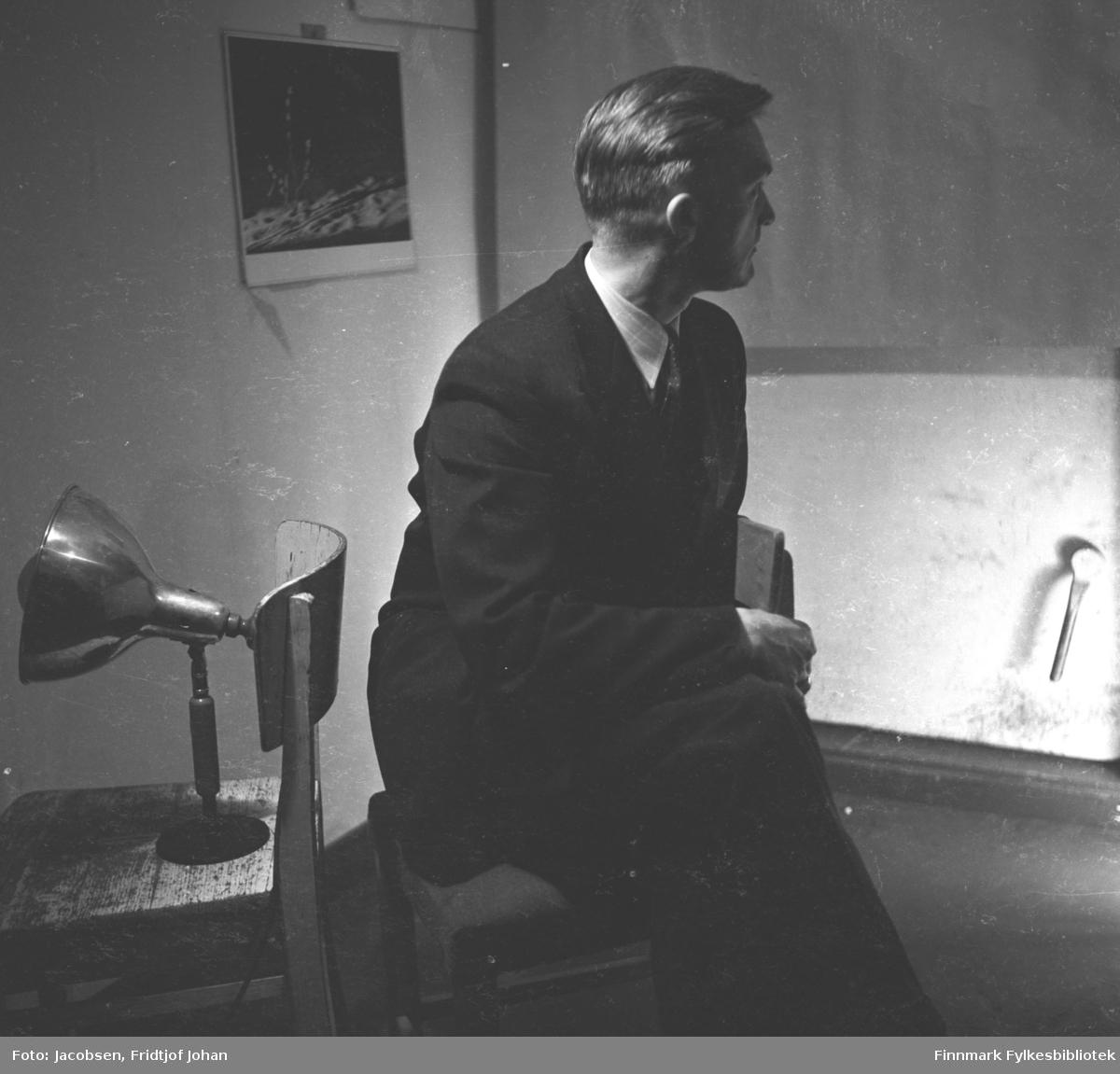Fridtjof Jacobsen sitter på en stol, iført mørk dress og hvit skjorte og slips. En pinnestol står ved siden av han. En liten lampe står på setet og en kalender henger på veggen oppe til høyre på bildet.