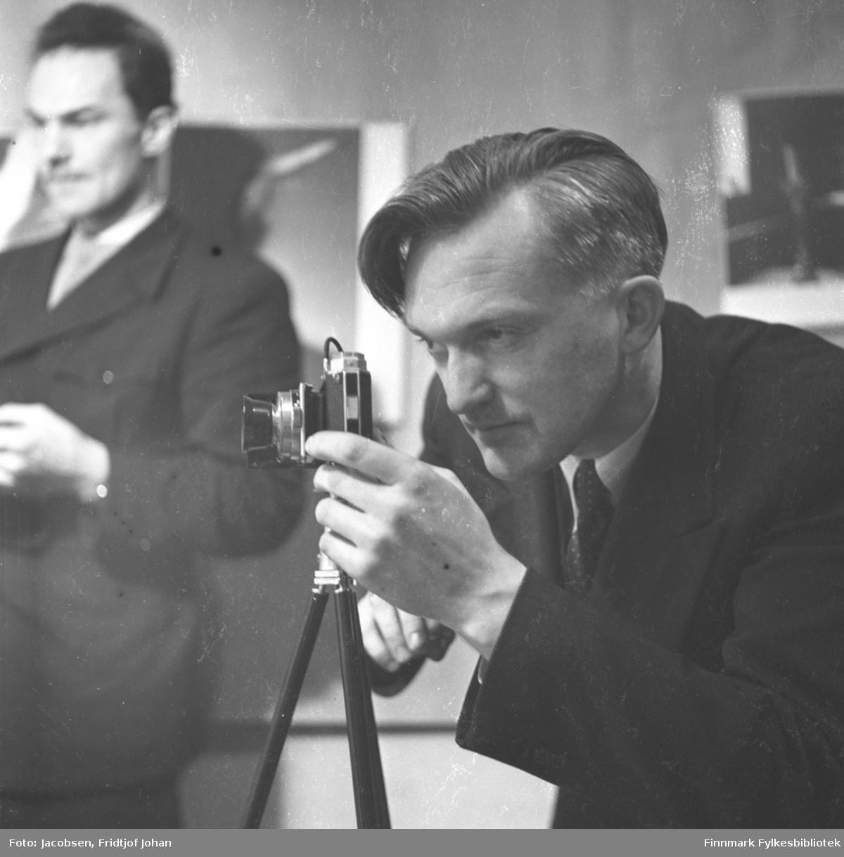 Fridtjof Jacobsen fotografert av Alf Edvard Jacobsen mens han selv fotograferer. Han har en mørk dress med hvit skjorte og slips på seg. Kameraet står på et stativ. En mann i mørk dress, hvit skjorte og slips står til venstre på bildet.