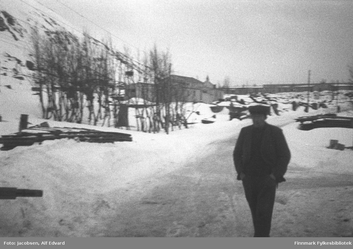 Bilde tatt vinteren 1946 i Hammerfest. Personen på bildet er ukjent. Han har mørke klær og lue på seg og har hendene i bukselommene. I bakgrunnen står gravkapellet, som var den eneste bygningen som stod igjen i Hammerfest etter tyskernes ødeleggelser. Noen få trær står mellom kapellet og fotografen. Fjellet Salen til venstre på bildet er nesten helt snødekt, bare noen få steiner vises gjennom snøen. Rester av det som ser ut som grunnmurer står igjen til venstre og helt til høyre på bildet. En brakke er satt opp foran kapellet og i horisonten ses en lang rekke med lave bygninger, muligens brakker. På høyde med hodet til mannen ses kirkegården. Pga snøen ses ikke gravstøttene, men de står der fremdeles så de ble også spart for ødeleggelsene. Noen el-stolper står igjen og en strømledning ses hengende oppe til venstre på bildet.