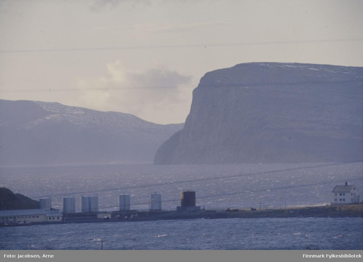 Essos tankanlegg på Rypklubbeidet. Kaia med lagerbygningen til venstre nede til venstre og neset på Rypklubben kommer ned bak lageret. Til høyre ligger et hus som tilhører anlegget. Sjøen nærmest er Rypefjorden og bak eidet er Sørøysundet. Del av øya Håja til høyre på bildet og Seiland til venstre. Litt snø på toppen av Håja og et tynt snølag ligger på Seiland også. En del vind fra Sør-Sørøst, men ellers bra høstvær.