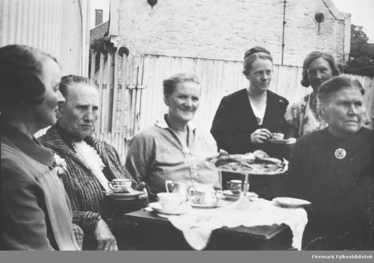 Fotografi av seks damer som sitter omkring et bord ute. Damen til venstre er lærerinne Julie Jacobsen fra Vardø. Hun var datter til smedmester i Vardø Ole Sigfrid og hustru Anna Christine Vibe Jacobsen. Det ligger en hvit duk på bordet. Oppå står det et stettfat med med småkaker. Der står også noen kopper og tefat, og et fløtesett. To av kvinnene holder kopp og tefat i hånden. I bakgrunnen ser man en stor murbygning. Det er et høyt tregjerde imellom