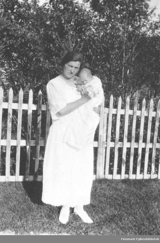 Fotografi av ukjent kvinne med et lite barn som hun holder. Hun står ute med et trestakittgjerde bak seg. Det er trær i bakgrunnen. Kvinnen er kledt i en hvit kjole, hvite strømper og hvite sko. Barnet er kledt i en hvit dåpskjole