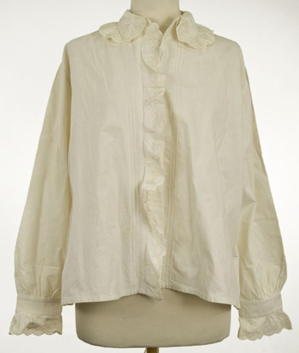 Hvit bomullsskjorte med blonde på ermer og krage.
