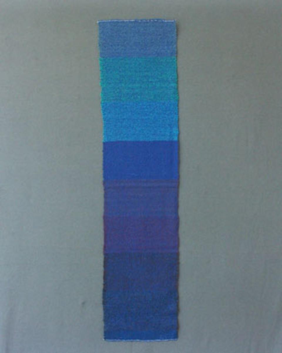 Prov till scarves vävd i tuskaft med blått ullgarn i varp och grått, brunt, lila, blått, blågrönt och grönt ullgarn i inslag.