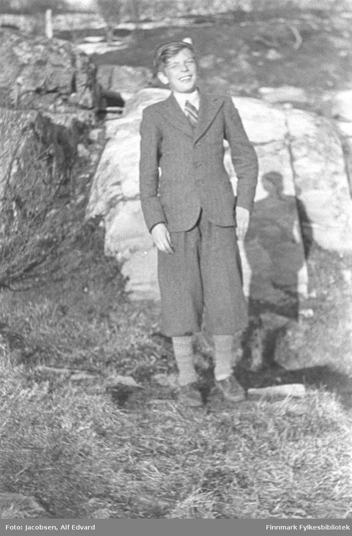 Øystein Nakken, Aase Jacobsens yngste bror, fotografert en solskinnsdag. Han har en forholdvis lys dress på seg. En lys skjorte og et stripet slips ses i halsen. Dressbuksa går bare til knærne og han har lyse strømper og mørke sko på seg. En ganske stor stein ligger i terrenget rett bak han og der vises også skyggen av han. Flere steiner ses oppover bakken til venstre på bildet. Der han står er bakken gresskledt og øverst på bildet ses en stolpe og flere mindre trær. Noen snøflekker ligger på bakken enda så bildet er nok tatt sent på våren.