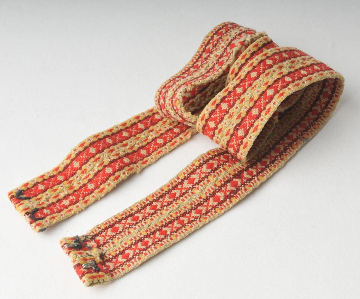 Vove belte som er sett saman av to smalare belte. Dei er sydde saman i høgda. To hemper i enden. slitt.