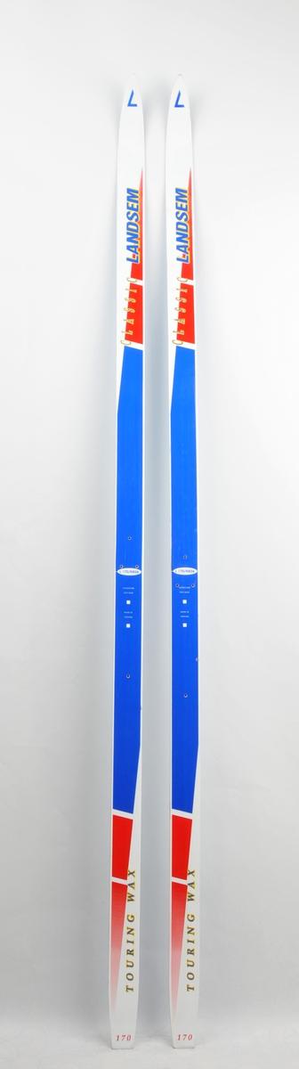 Langrennski laga av glasfiber. Kvit overflate, raud, blå og gul dekor/skrift. Blå såle av plast. Det har vore bora hol til bindingar.