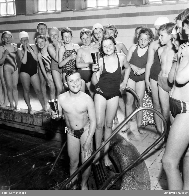 Simtävling för folkskolans tredjeklassare pågår för fullt i det gamla badhuset på Kyrkogatan i centrala Sundsvall. På tredje bilden poserar de båda vinnarna i pojk- respektive flickfinalen, Hans Norlin och Irma Åstrand, med sina pokaler. Anläggningen var när den invigdes 1908 toppmodern med sin 7.90x14.65 meter stora bassäng. Badhuset användes fram till 1971 och revs 1973 då det var kraftigt angripet av träsvamp och ansågs för dyrt att renovera.