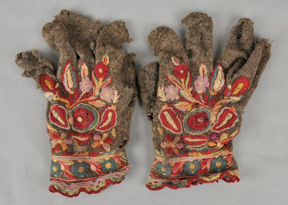"""Strikka fingervottar i tynt, 2 tråds, grått, naturfarga spelsau-ullgarn. 4 masker pr cm. Rosesauma med ullgarn (zephyrgarn) på øvre kanten, på handbaken og på tommelen. Rundt øvre kanten er det ein blondekant hekla i same garn som broderiet (av R. Berge kalla """"agramanvovne uvled kantar"""")."""