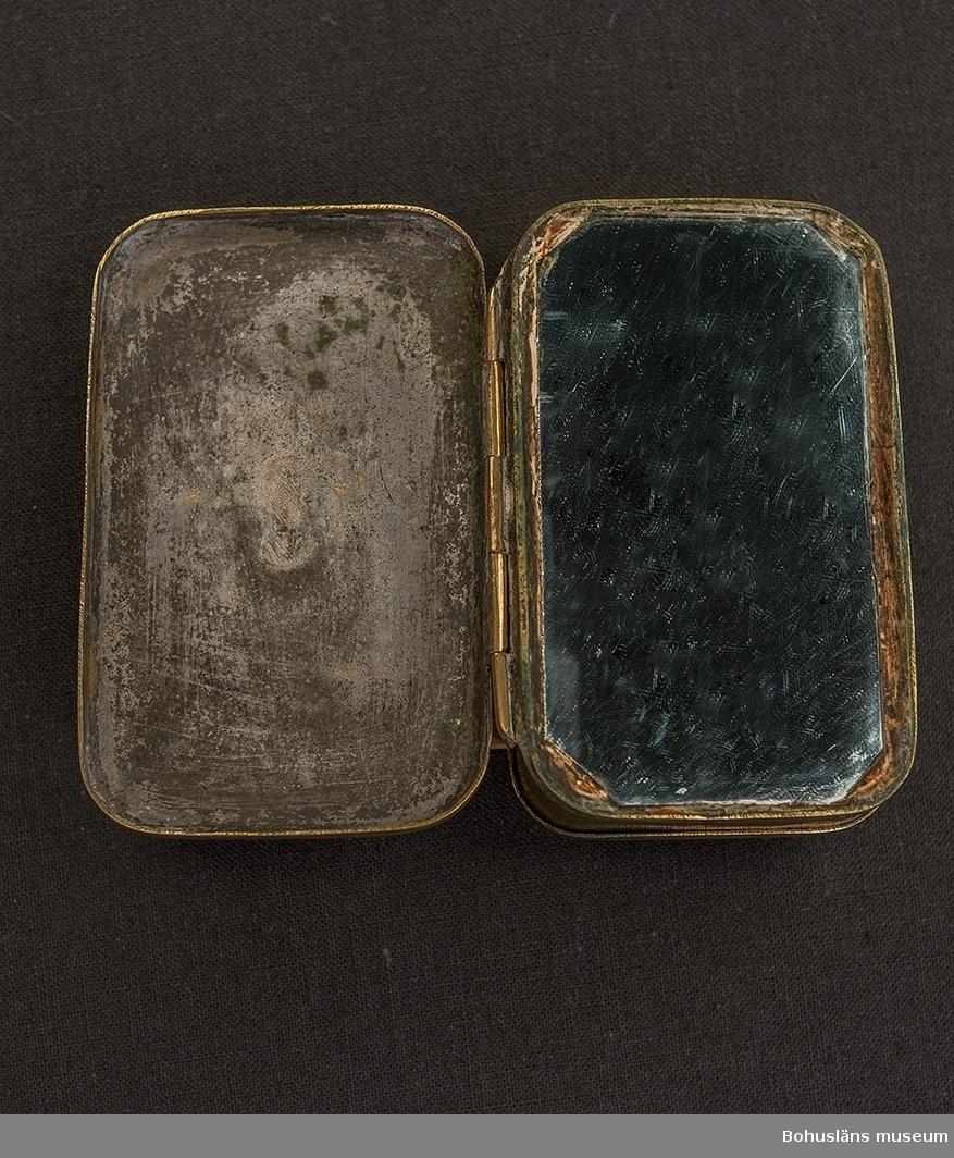 Rektangulär mässingsdosa med två öppningsbara lock och spegel.  Invändigt med sliten förtenning. Framsidans lock med präglat mönster föreställande vy över Stockhoms slott, fasad mot öster. Ovan byggnaden texten KONGLIGA SLOTTET, i övre högra hörnet GUSTAF ADOLPH ovan en kungastaty på sockel. Inuti dosan ligger en järnkam, se UM032062. Baksidans lock stämplad S. A. BERG (otydligt) I dosan ett spegelglas, troligen ej samtida. Dosan är sliten.  I dosan förvaras också en handskriven papperslapp, trol. skriven av Apollo Antik, med texten: Kongl. Slottet Gustav IV Adolf Dosa + järnkam