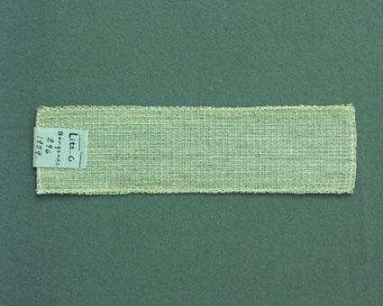 Ljusgrått möbeltygsprov vävt i fantasibindning enligt tidigare inventering, med bomullsgarn i varp och ull- och lingarn i inslag. Ytterligare prov och vävuppgifter finns i pärm Möbeltyg b och Möbeltyg c, litt c 296.