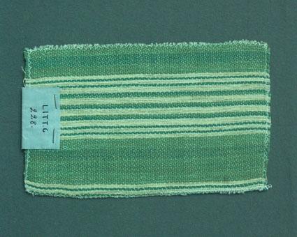 Randigt möbeltygsprov i grönt och oblekt, vävt i korskypert med bomullsgarn i varp och lin- och ullgarn i inslag. Ytterligare prov och vävuppgifter finns i pärm Möbeltyg a, litt c 228.