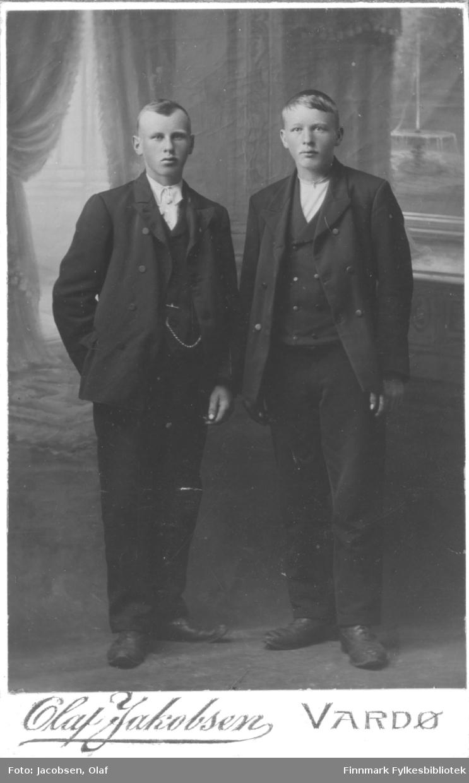 Portrett av to unge menn kledd i mørke dresser, hvite skjorter og vester. Gutten til venstre har lommeur i ei lenke.  Albumet med bildet kommer fra Ekkerøy, kanskje de kommer derfra.